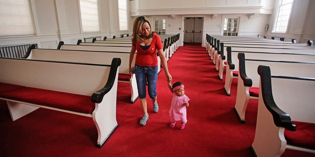 Vicky Chavez walks with her daughter Issabella in the First Unitarian Church, in Salt Lake City. Chavez, a Honduran woman who came to the U.S. four years ago seeking asylum from an abusive boyfriend, says she'll continue taking sanctuary in the church where she's been for the past six months with her two young daughters despite being ordered to leave and exhausting her appeals.