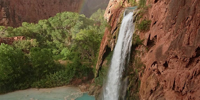 A rainbow appears over a waterfall on the Havasupai reservation in Supai, Ariz., Wednesday, July 11, 2018.