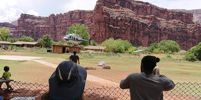 A helicopter lands to rescue people from flooding on the Havasupai reservation in Supai, Ariz., Thursday, July 12, 2018.