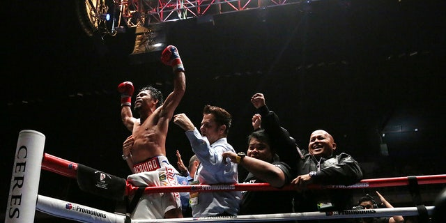 Manny Pacquiao of the Philippines, left, celebrates after defeating Lucas Matthysse of Argentina during their WBA World welterweight title bout in Kuala Lumpur, Malaysia