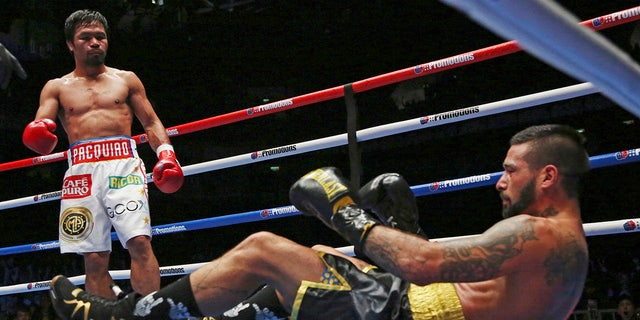 Lucas Matthysse, left, of Argentina falls after receiving a punch by Manny Pacquiao of the Philippines during their WBA World welterweight title bout in Kuala Lumpur, Malaysia.