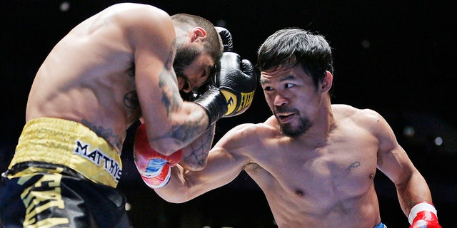 Manny Pacquiao of the Philippines, right, strikes Lucas Matthysse of Argentina during their WBA World welterweight title bout in Kuala Lumpur, Malaysia, Sunday, July 15, 2018. Pacquiao won the WBA welterweight world title after a technical knockout in round seven. (AP Photo/Yam G-Jun)