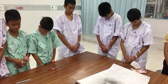 Some of the rescued soccer team members bowing their heads respectfully in front of a sketch of the Thai Navy SEAL diver who died while trying to rescue them.