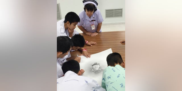 In this photo released by In this photo released by Thailand's Ministry of Health and the Chiang Rai Prachanukroh Hospital, some of the rescued soccer team members autographs and write notes on a sketch of the Thai Navy SEAL diver who died while trying to rescue them.
