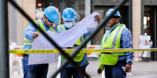 Con Edison workers look at a map of pipes on New York's Fifth Avenue, Thursday, July 19, 2018.