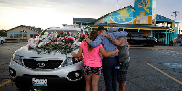 People pray by a car thought to belong to a victim of Thursday's boating accident before a candlelight vigil in the parking lot of Ride the Ducks Friday, July 20, 2018, in Branson, Mo.