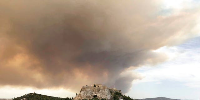 At least 20 people have been killed and dozens more injured as two huge wildfires burned outside of Athens, Greece, officials announced Tuesday.