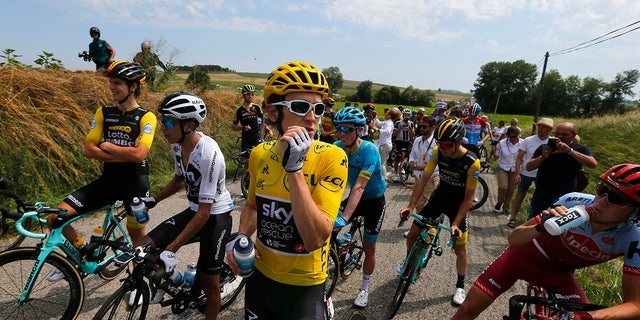 Riders with Britain's Geraint Thomas, wearing the overall leader's yellow jersey, wait on the road after a farmer's protest interrupted the sixteenth stage of the Tour de France.