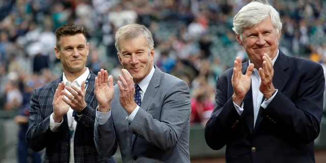 Seattle Mariners general manager Jerry Dipoto, left, president Kevin Mather, center, and majority owner John Stanton applaud during a presentation before a baseball game against the Detroit Tigers in Seattle, May 18, 2018.