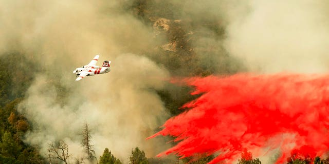 An air tanker drops retardant while fighting to stop the Ferguson Fire from reaching homes in the Darrah community of unincorporated Mariposa Count, Calif., Wednesday, July 25, 2018.