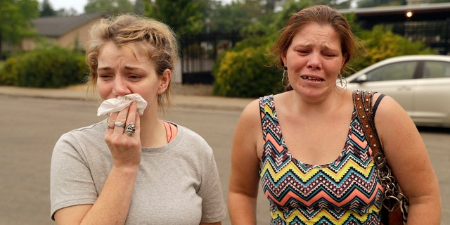 Sherry Bledsoe, left, cries next to her sister, Carla, outside of the sheriff's office after hearing news that Sherry's children, James and Emily, and grandmother, Melody Bledsoe, were killed in a wildfire Saturday, July 28, 2018, in Redding, Calif.