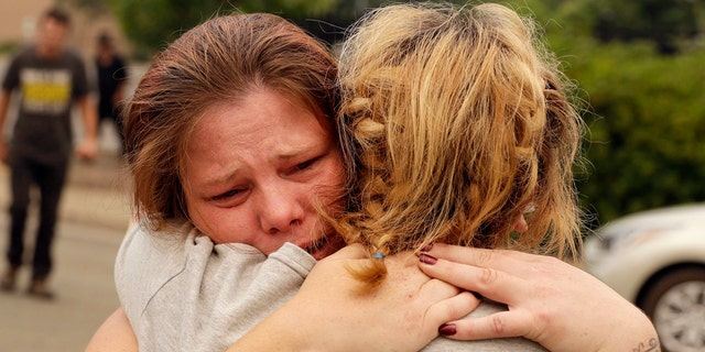 Carla Bledsoe, facing camera, hugs her sister Sherry outside of the sheriff's office after hearing news that Sherry's children James, 4, and Emily 5, and grandmother were killed in a wildfire Saturday, July 28, 2018, in Redding, Calif.