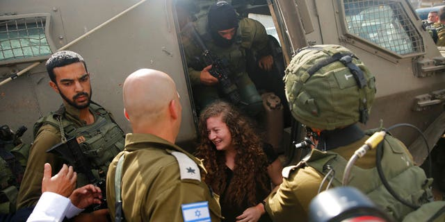 Ahed Tamimi exits an armored military vehicle as she is released by the Israeli8 army Israeli prison after serving an eight month sentence at the entrance of her village of Nebi Saleh in the West Bank Sunday, July 29, 2018.