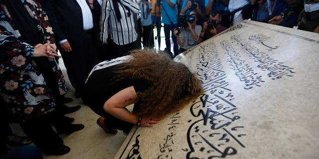 Ahed Tamimi prays at the tomb of former Palestinian leader Yasser Arafat in the West Bank city of Ramallah, Sunday, July 29, 2018.