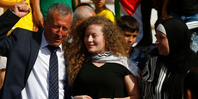 Ahed Tamimi stand between her father Bassam and mother Nariman during a press conference on the outskirts of the West Bank village of Nabi Saleh near the West Bank city of Ramallah, Sunday, July 29, 2018.