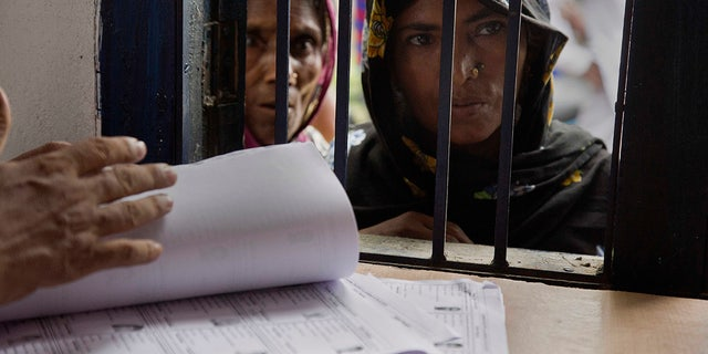 Muslim women stand in a queue to check if their names are included in the National Register of Citizens at a draft center in Mayoung.