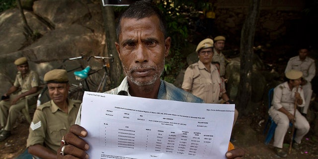 Muhammed Mainuddin, shows his name on a sheet collected from the National Register of Citizens draft center in Mayoung, about 55 kilometers (34 miles) east of Gauhati, India