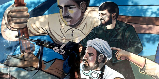 An Iranian woman walks past a mural depicting members of Basij paramilitary force, portraying Iranians' solidarity against their enemies, painted on the wall of a government building at the Felestin (Palestine) Sq. in downtown Tehran