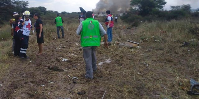 "Rescue workers and firefighters are seen at the site where an Aeromexico airliner has suffered an ""accident"" in a field near the airport of Durango, Mexico, Tuesday, July 31, 2018."