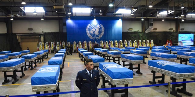 A U.S. airman stands guard next to caskets containing remains of U.S. soldiers killed in the Korean War and collected in North Korea before a repatriation ceremony at Osan Air Base in Pyeongtaek, South Korea, on Wednesday, Aug. 1, 2018.