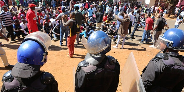 Police block dozens of opposition party supporters from entering the Zimbabwe Electoral Commission offices in Harare, Zimbabwe.
