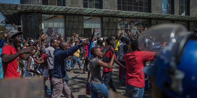 Angry opposition supporters gathered outside Zimbabwe's electoral commission and were met by riot police on Wednesday as the country awaited the results of Monday's presidential election.