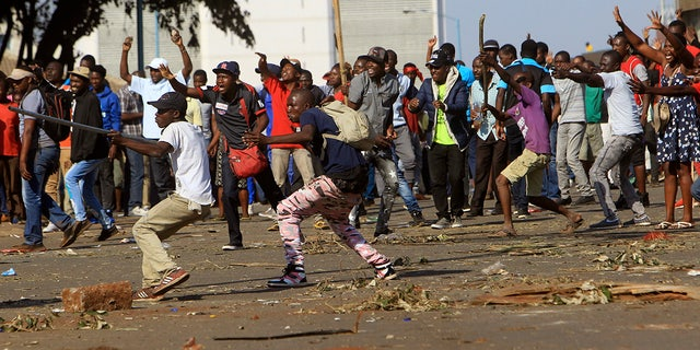 Opposition party supporters react after police fired tear gas, in Harare, Zimbabwe.
