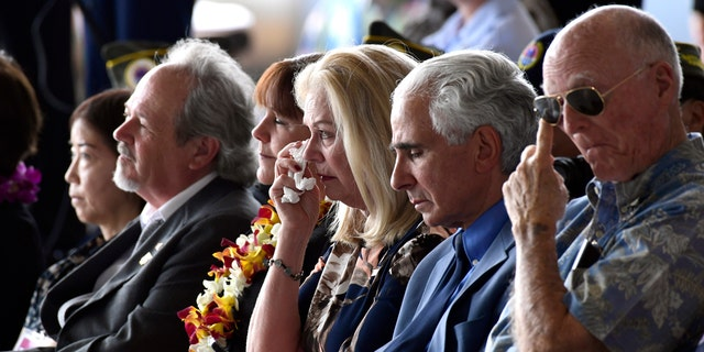 Robert Sanfilkippo, second right, sits next to his wife, Diana Brown Sanfilippo who has spent a lifetime searching for her father, 1st Lt. Frank Salazar who died 66 years ago in North Korea, who wipes her eyes as she sits in the audience with Karen Pence, wife of Vice President Mike Pence, at a ceremony marking the arrival of the remains believed to be of American service members who fell in the Korean War at Joint Base Pearl Harbor-Hickam, Hawaii, Wednesday, Aug. 1, 2018. Second from left is Rick Downes, who was three when his father Hal went off to the Korean War, and he has been missing ever since.