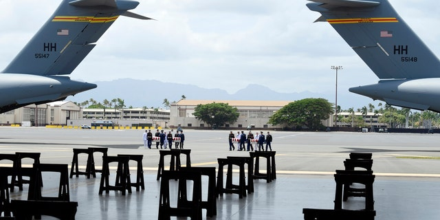 Military members carry transfer cases from a C-17 at a ceremony marking the arrival of the remains believed to be of American service members who fell in the Korean War at Joint Base Pearl Harbor-Hickam in Hawaii, Aug. 1, 2018.