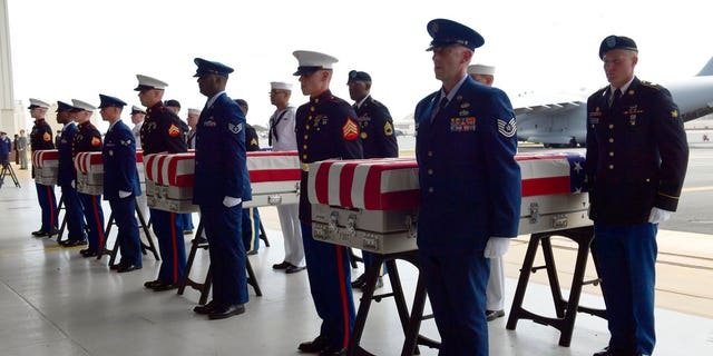 Military members stand at attention after placing transfer cases in a hanger at a ceremony marking the arrival of the remains believed to be of American service members who fell in the Korean War at Joint Base Pearl Harbor-Hickam in Hawaii, Wednesday, Aug. 1, 2018.