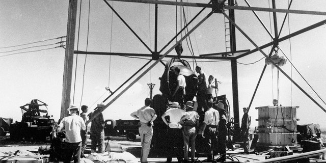 In this July 6, 1945, file photo, scientists and workmen rig the world's first atomic bomb to raise it up onto a 100 foot tower at the Trinity bomb test site near Alamagordo, N.M.
