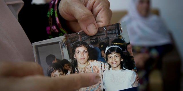 Fadwa Tlaib, an aunt of Rashida Tlaib points to a young Rashida in a 1987 picture with her mother Fatima and brother Nader, at the family house, in the West Bank village of Beit Ur al-Foqa.