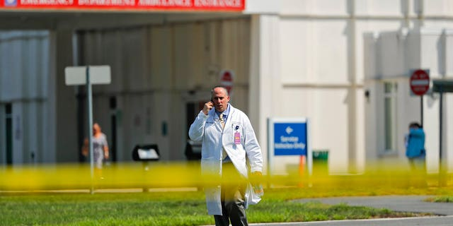 A physician walks out of the emergency entrance to Westchester Medical Center, Wednesday, Aug. 8, 2018, in Valhalla, N.Y.