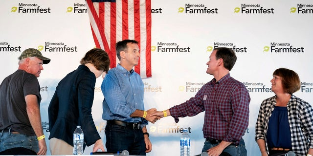 Minnesota gubernatorial candidates Tim Pawlenty, center left, and Jeff Johnson shake hands as fellow candidates look on at the end of a forum.