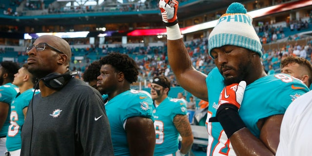 Miami Dolphins defensive end Robert Quinn (94) raises his right fist during the singing of the national anthem, before the team's NFL preseason football game.