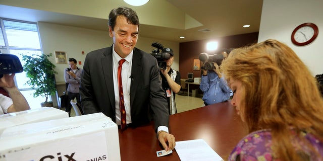 In this July 15, 2014 file photo, Silicon Valley venture capitalist Tim Draper presents his drivers license as he turns in boxes of petitions for a ballot initiative that would ask voters to split California into six separate states in Sacramento, Calif.