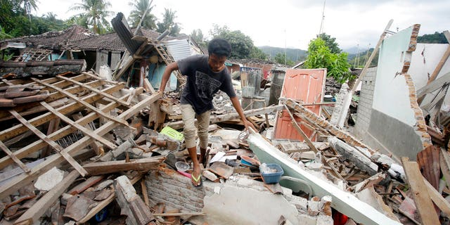 A man walks through debris from Sunday's earthquake in West Lombok, Indonesia, Saturday