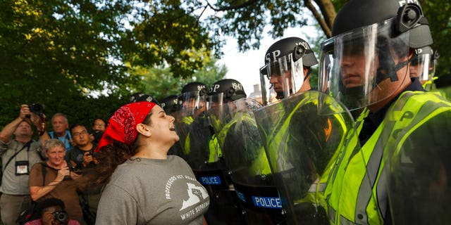 """Emily Filler attempts to dissuade state police from advancing on students rallying on the grounds of the University of Virginia on the anniversary of the """"Unite the Right"""" rally in Charlottesville."""