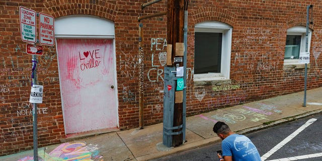 Ahmed Mohamed writes a message on the ground of the alleyway where a memorial for Heather Heyer, who was killed during last year's Unite the Right rally, is located in Charlottesville, Va.