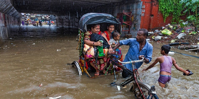 An Indian rickshaw puller transporting two women and a child wades through a water logged street following heavy rains in Allahabad, India, Sunday, Aug. 12, 2018. India gets its monsoon rains from June to September. (AP Photo/Rajesh Kumar Singh)