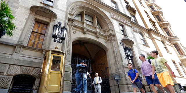People walk by the entrance to the Dakota Apartments, in New York on Aug. 15, 2018, where John Lennon was shot by Mark Chapman in 1980.