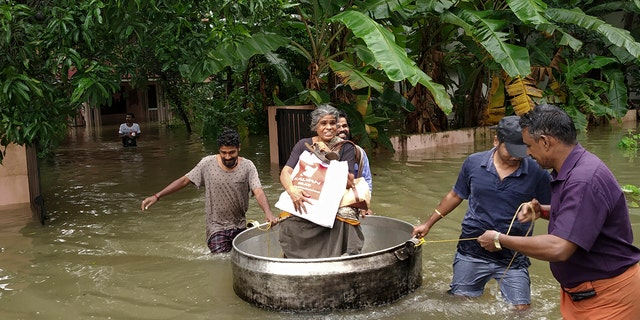 An elderly woman is rescued in a cooking utensil after her home was flooded in Thrissur, Kerala state, India.