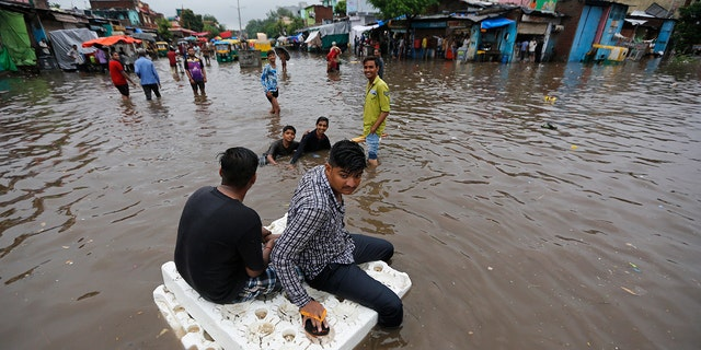 Indian men use thermocol sheets as a makeshift raft on a flooded road after heavy rainfall in Ahmadabad, India.