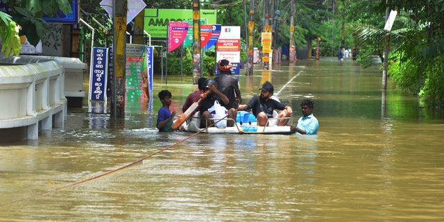 People move past a flooded area in Thrissur, in the southern Indian state of Kerala, Friday, Aug. 17, 2018.