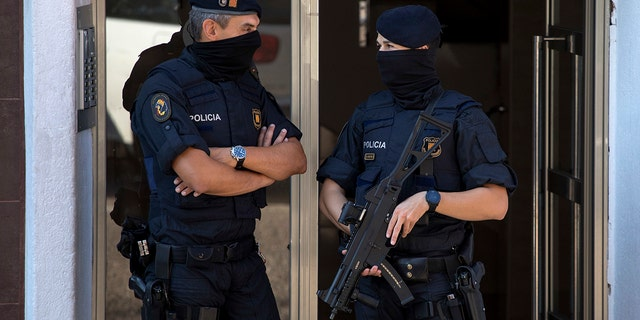 Catalan police officers stand guard at the entrance of a building during a raid, following an attack in Cornella de Llobregat near Barcelona, Spain
