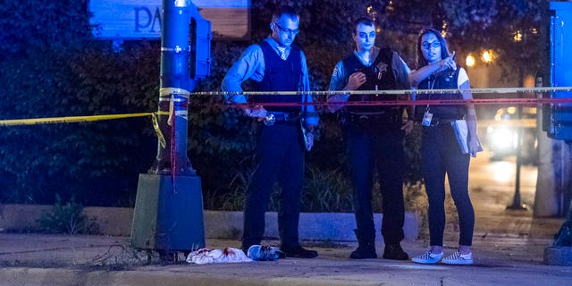 Chicago Police investigate the scene where someone was shot Sunday, Aug. 19; the weekend was the second most violent this year