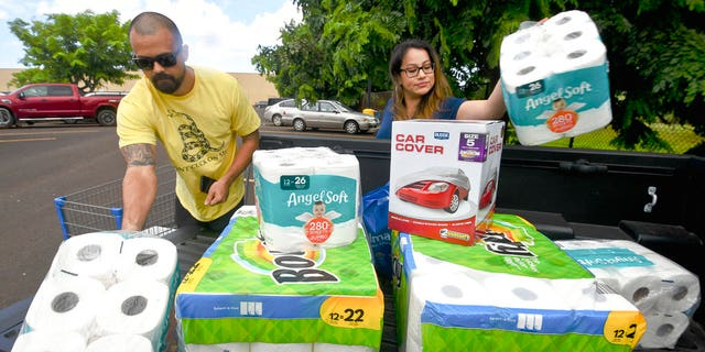 Bryce and Dom Boeder of Waimea, Kauai, load their truck with storm supplies in the parking lot of a Walmart store in Lihue, on the island of Kauai, Hawaii, Tuesday, Aug. 21, 2018.