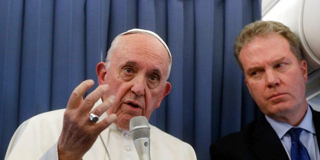 Pope Francis, flanked by Vatican spokesperson Greg Burke, listens to a journalist's question during a press conference aboard of the flight to Rome at the end of his two-day visit to Ireland, Sunday