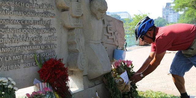 Pham Van Khanh, a 62-year-old retiree, lays flowers at the monument of Senator John McCain in Hanoi, Vietnam.