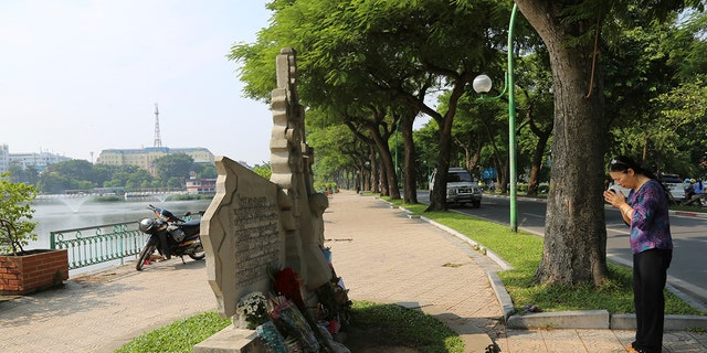 A woman pays respect at the monument of the late U.S. Senator John McCain in Hanoi, Vietnam.